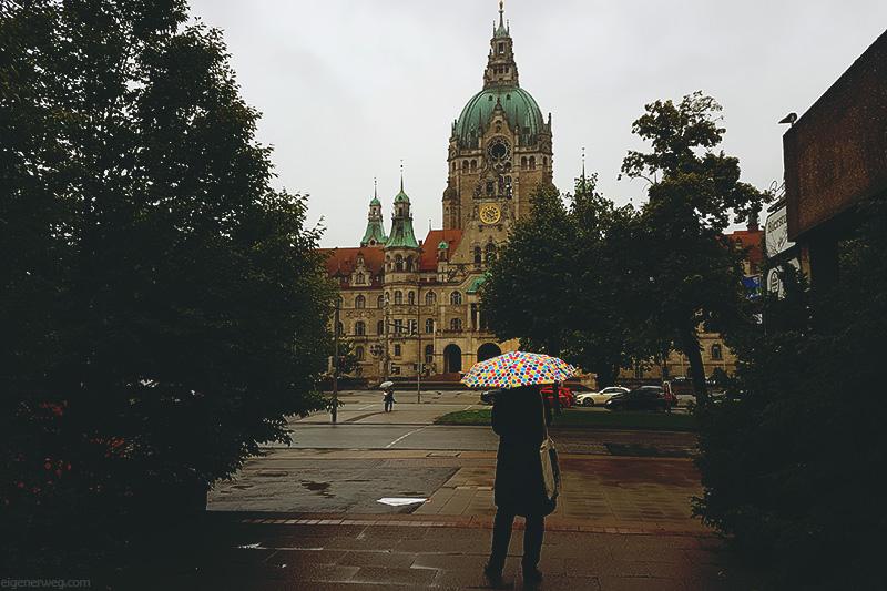 Frau mit Regenschirm vor dem neuen Ratshaus